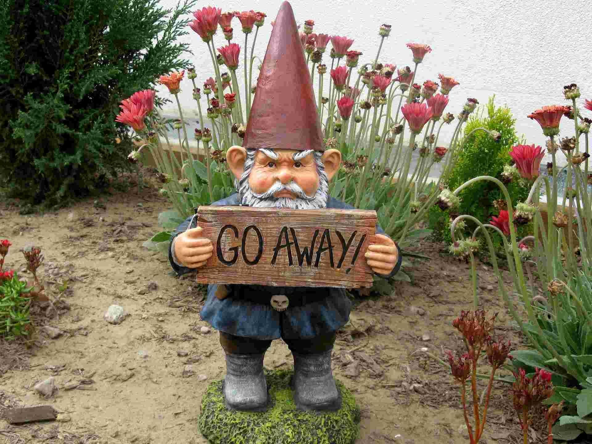 Скульптура в виде злого гнома в частном саду
