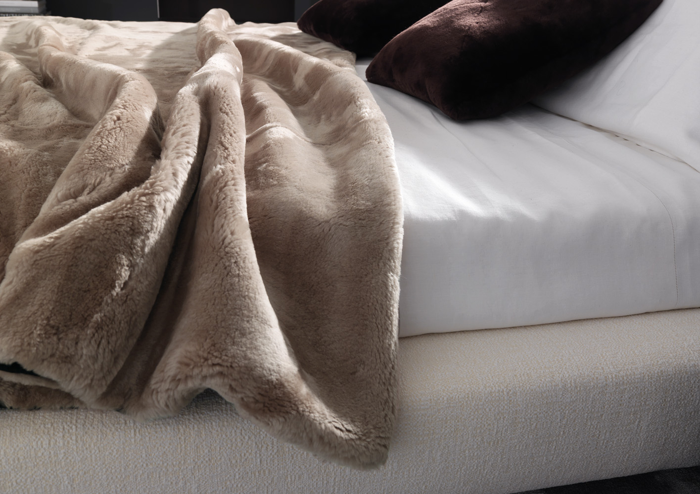Плед из серого меха на кровати