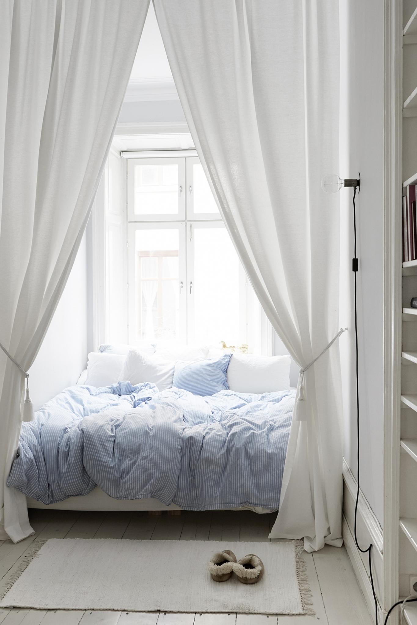 Кровать изголовьем к окну со шторами