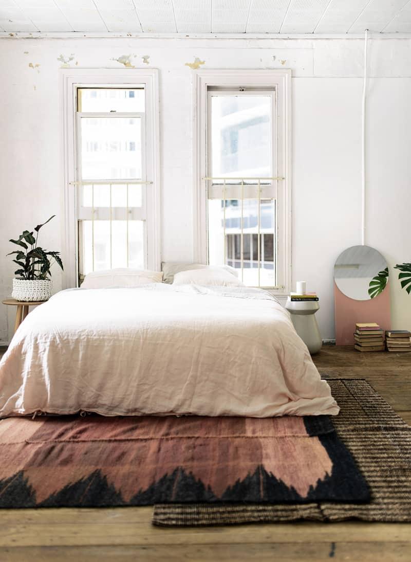 Кровать изголовьем к окну в современной спальне