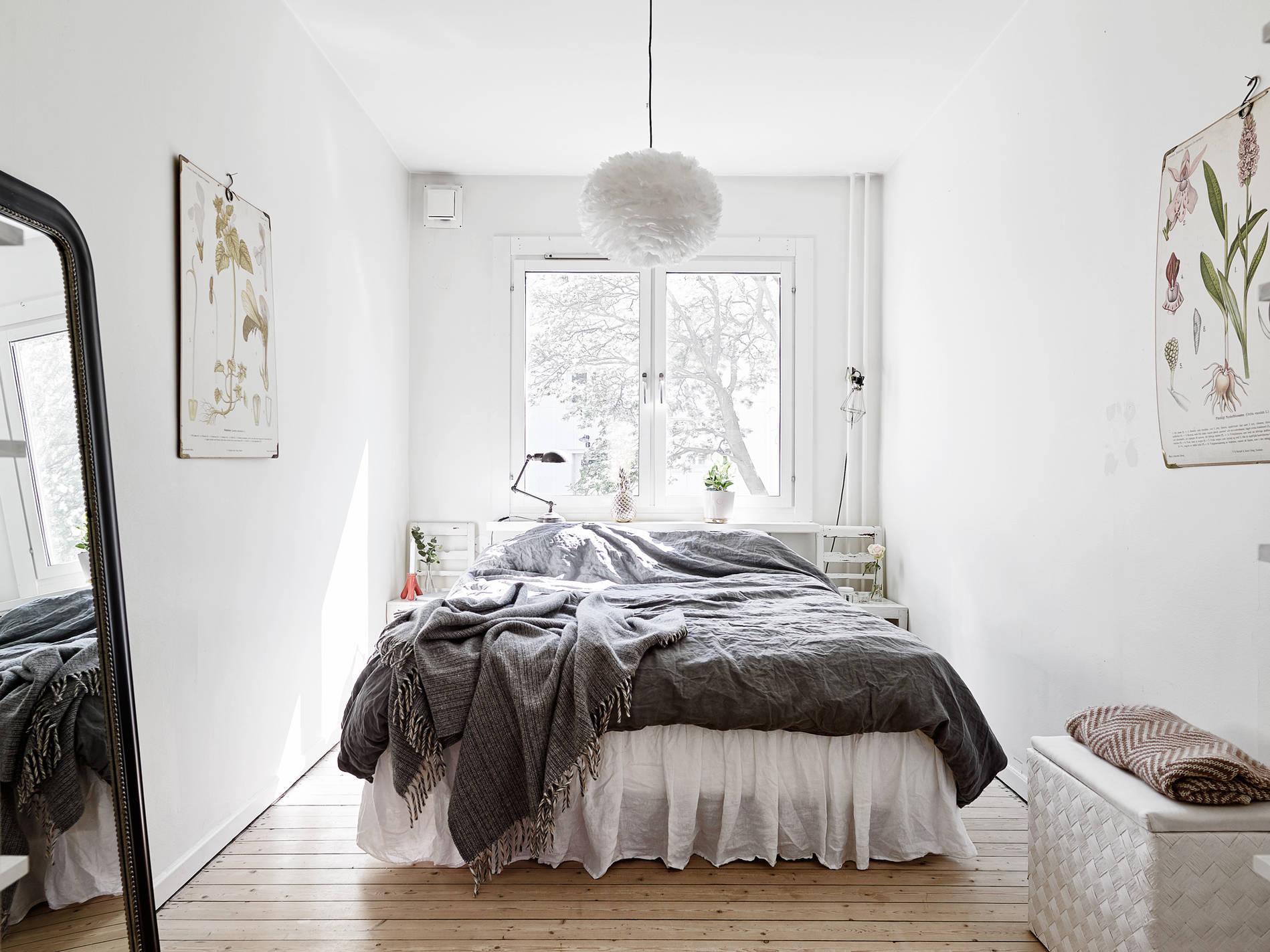 Кровать изголовьем к окну в спальне в скандинавском стиле