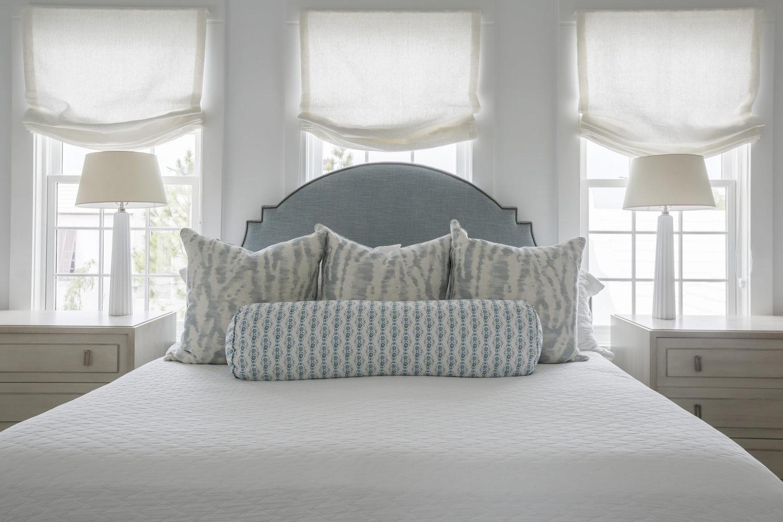 Кровать изголовьем к трем окнам в спальне