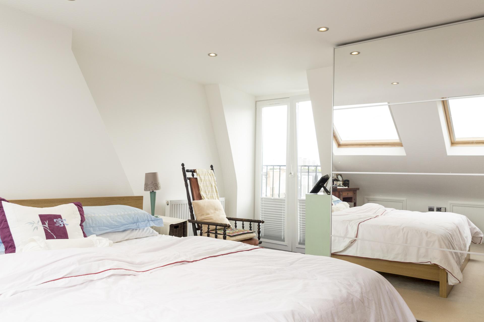 Кровать изголовьем к окну в спальне с зеркалом