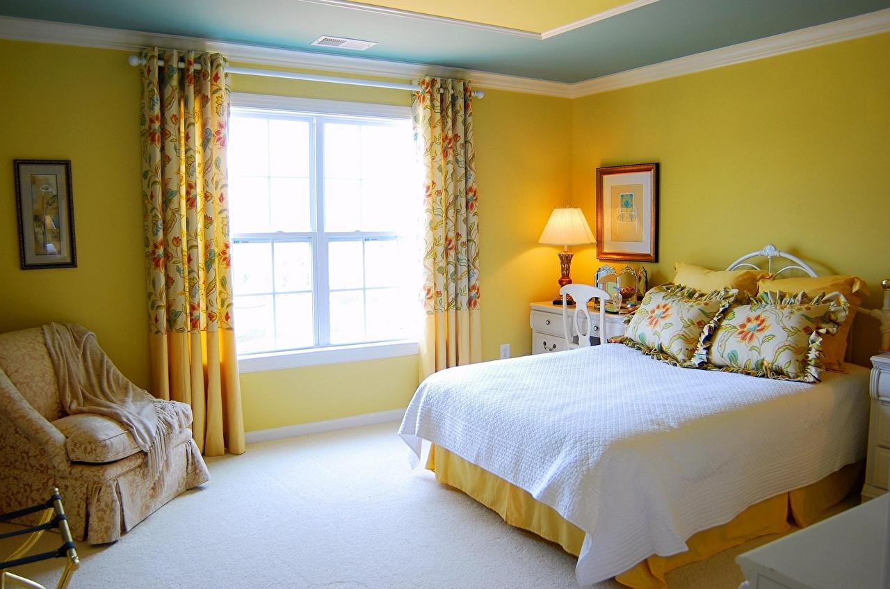 Кровать изголовьем к окну в спальне желтой
