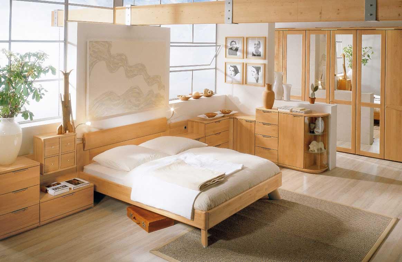 Кровать из массива дерева в интерьере спальни