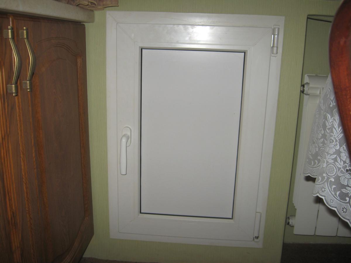 Холодильник под окном с дверкой