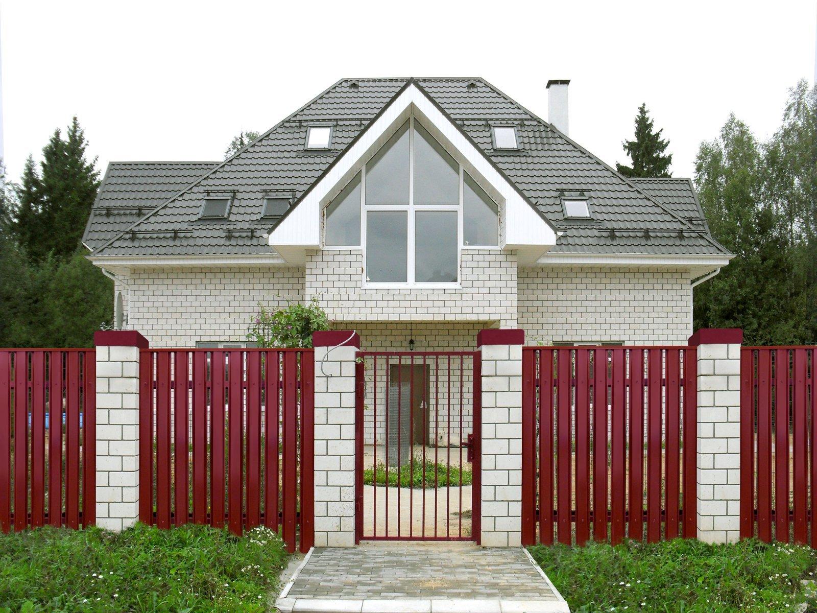Забор из красного штанкетника с кирпичными столбами