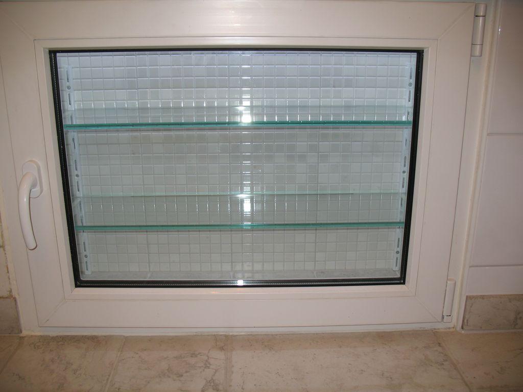 Холодильник под окном со стеклянными полками
