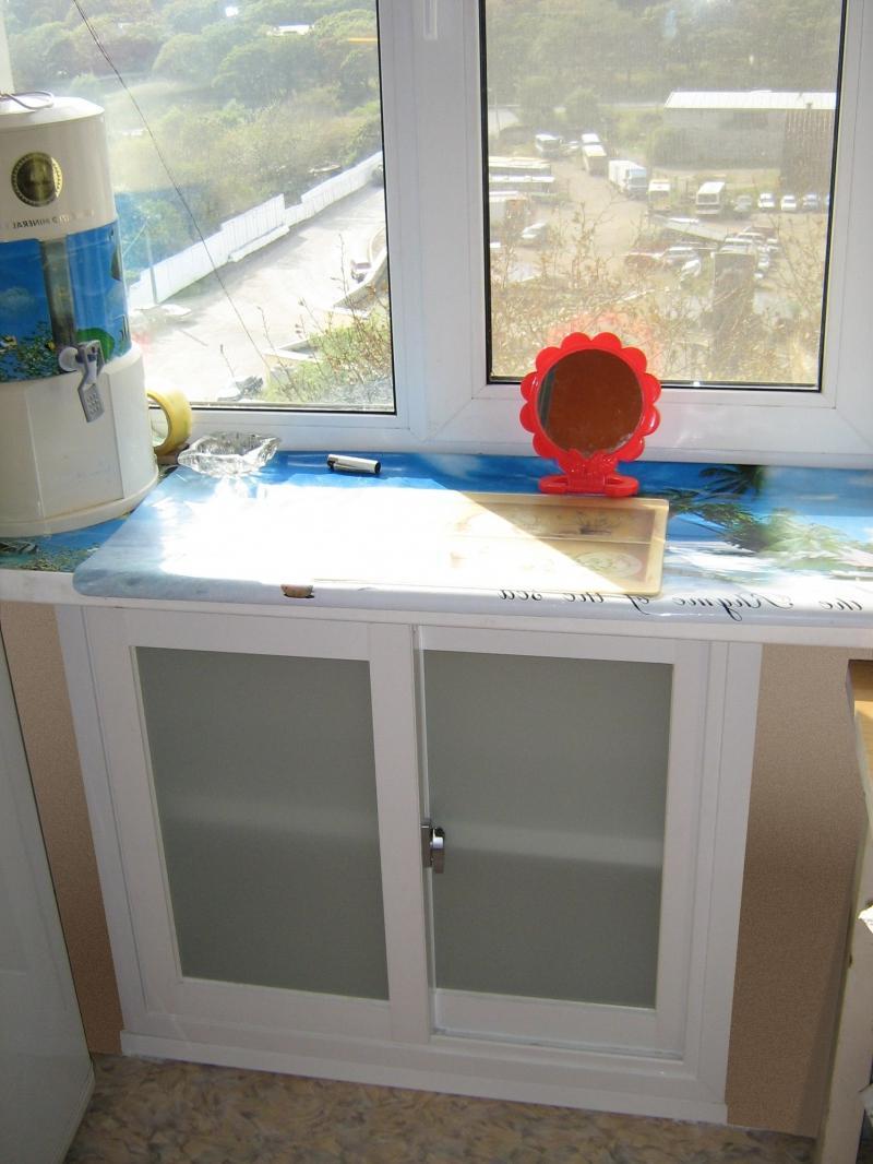 Холодильник под окном со стеклянными дверками