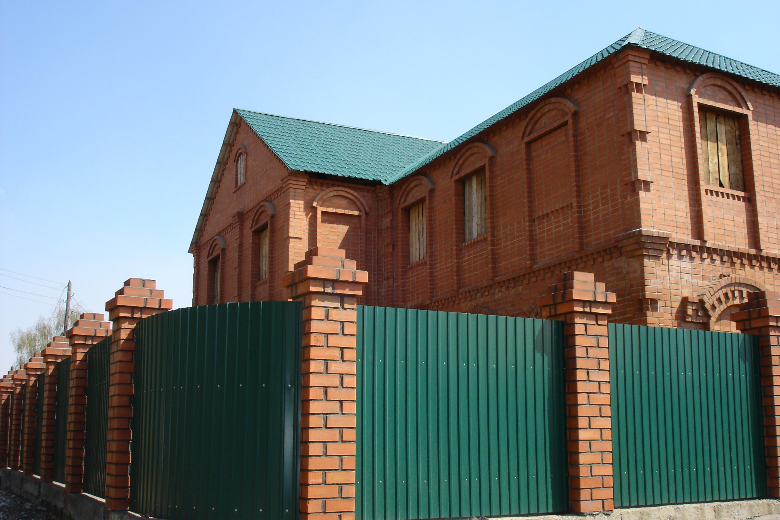 Забор из зеленого профлиста с кирпичными столбами