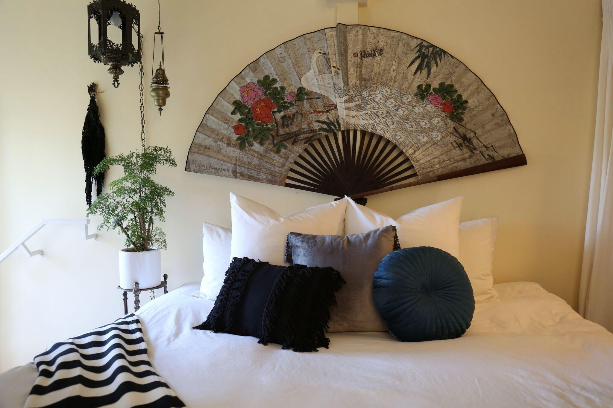 Веер с павлином на стене спальни