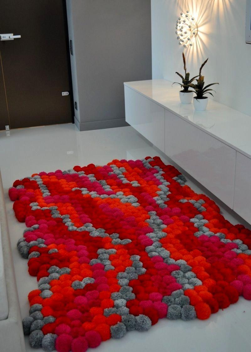 Красный коврик из помпонов в прихожей