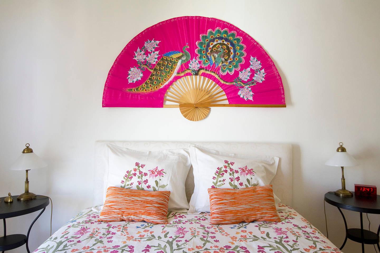 Настенный розовый веер в интерьере спальни
