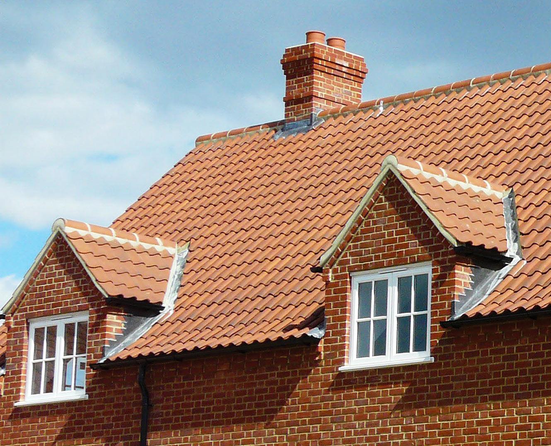 Кирпичный дом с керамической черепицей на крыше