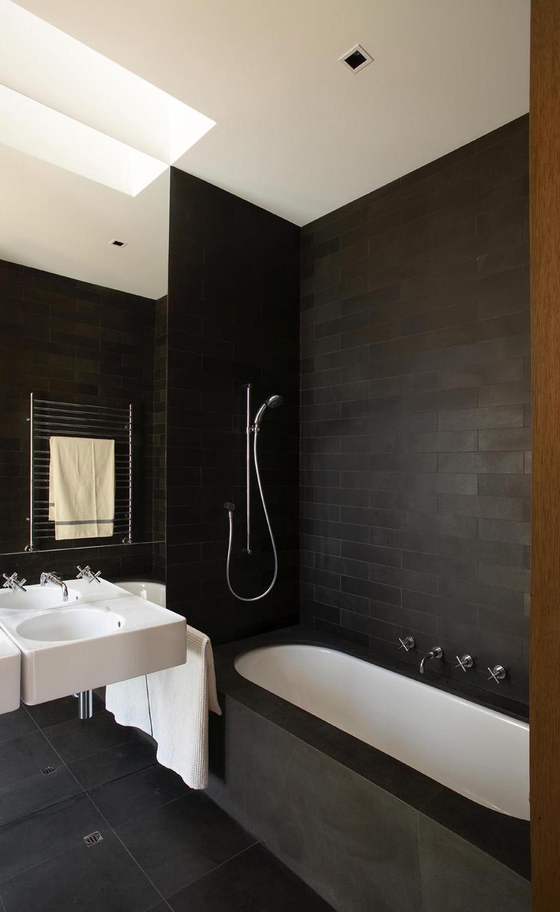 Черная каменная плитка в белой ванной